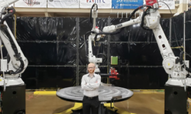 Justin Nussbaum standing in front of large-scale metal additive manufacturing machine